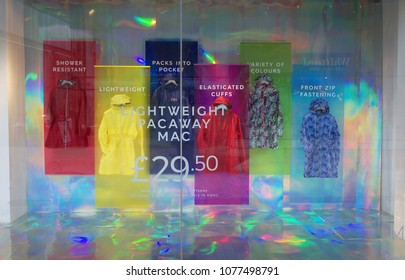 Bracknell, England - April 12, 2018: Colorful window display of rain macs and shower proof coats in the Marks & Spencer Department Store located in Bracknell, England
