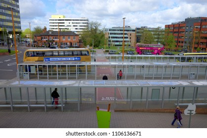 Bracknell, England - April 25, 2018: A view of pedestrians and buses at the main bus station in front of buildings which form part of the downtown area of Bracknell in England