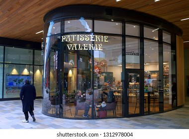Bracknell, England - April 30, 2018: People inside and a pedestrian passing by the Patisserie Valerie store in Bracknell, England. A chain of cafes specializing in hand-made cakes, teas and coffees