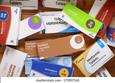 Bracknell, England - February 10, 2014: A wooden drawer full of drug boxes for medication including Warfarin, Metformin, Simvestatin and Amlodipine, from various manufacturers.