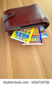 Bracknell, England - February 17, 2018: A wallet containing a selection of lottery scratch cards with cash prizes in British Pounds for the winner.