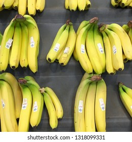Bracknell, England - February 20, 2019: Ripe yellow bananas displayed in bunches on a market stall in England