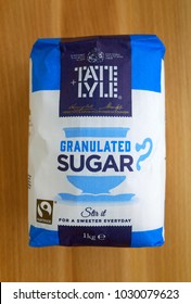 Bracknell, England - February 21, 2018: A one kilo bag of Tate & Lyle granulated sugar on a wooden background. Henry Tate and Abram Lyle merged their respective sugar businesses in London in 1921