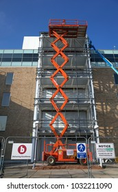 Bracknell, England - February 24, 2018: A Scissor Lift Access Platform made by Holland International in place and extended outside an office building undergoing refurbishment in Bracknell, England