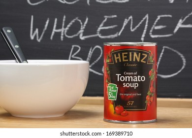 Bracknell, England - January 02, 2014: A tin of Heinz Cream of Tomato Soup next to a white bowl and in front of a blackboard. Heinz started manufacturing food products in the USA in 1869