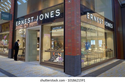 Bracknell, England - January 31, 2018: A man looking at the window display of  the Ernest Jones jewellery store in Bracknell, England. The company now has over 180 stores across the UK