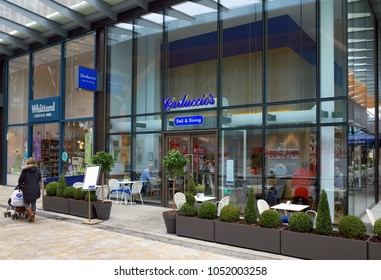 Bracknell, England - March 20, A woman with a pram passes by Carluccio's Deli & Dining in Bracknell, England with people visible through the windows. Antonio Carluccio started the business in 1999