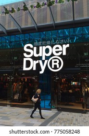 Bracknell, England - Nov 21, 2017: Pedestrian walking by the window display of the Superdry clothing store in Bracknell, England. Superdry is part of Supergroup PLC, a British clothing company