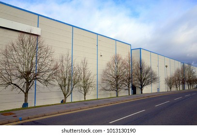 Bracknell,England - January 29, 2018: Wide angle view of warehouses in a row beside an empty tree-lined road on an industrial estate in Bracknell,England