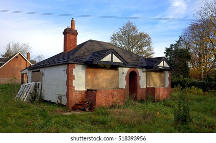Bracknell,England - November 19, 2016: Dilapidated cottage type house with boarded up windows and an overgrown garden in Bracknell, England