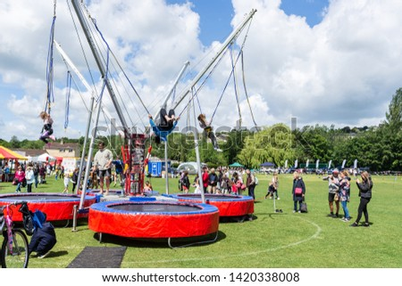 Bradford on Avon Wiltshire May 27th 2019 Children bouncing on a bungee trampoline while adults watch