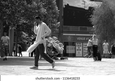 Bradford, West Yorkshire, England - 07/02/2018. Pakistani man on his mobile phone wearing track bottoms and kameez / qameez walking in Bradford city centre with blond white girl in background.
