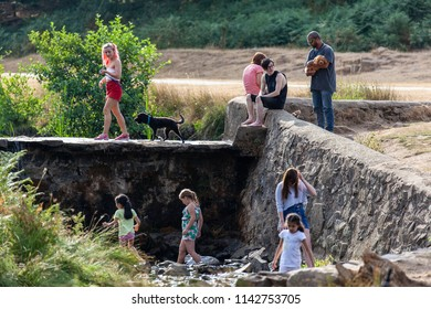 Bradgate Park, Leicestershire, England July 25th 2018: Children and adults enjoy playing in a dried-up up stream late evening on a hot summer night.