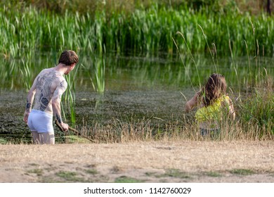 Bradgate Park, Leicestershire, England July 25 2018: England summer heatwave 2018 and a young couple (boy and girl) take to the water of a stream on a early evening hot summer night.