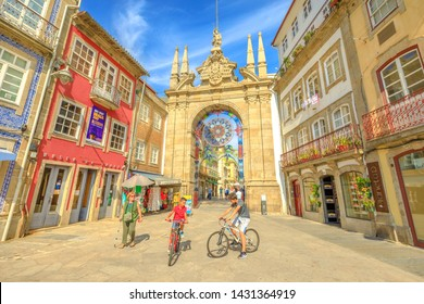 Braga, Portugal - August 12, 2017: children cycling in front of popular Arco da Porta Nova. Arch of New Gate in Baroque style is part of Braga city walls and is one of the oldest cities in Portugal.
