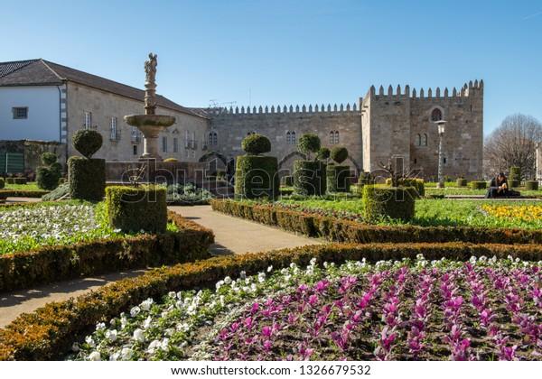 BRAGA, PORTUGAL - CIRCA FEBRUARY 2019: Santa Barbara garden with the medieval Episcopal Palace of Braga in background.