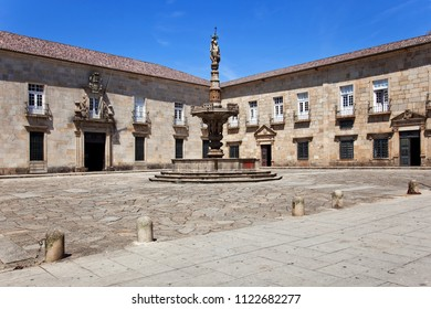 Braga, Portugal - July 27, 2015: Baroque Castelos Fountain in Paco Square, and the baroque facade of the Nursing School of the Minho University
