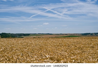 Brahmenau / Germany: Looking south from a freshly mown golden stubblefield over the hilly rural landscape in Eastern Thuringia to the small village of Gera-Trebnitz