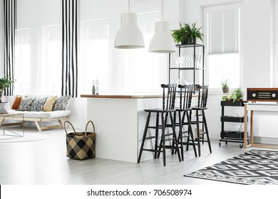 Braided basket on floor next to kitchen countertop with bar stools in room with vintage radio on shelf