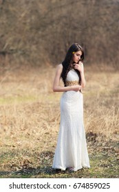Braided bride in white dress on blurred autumn background during a wedding photo shoot. Young beautiful woman with flowers in hair
