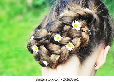 Braided brown hair with daisies closeup