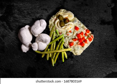 Braided buffalo mozzarella, boiled green beans and Russian salad on wet black slate