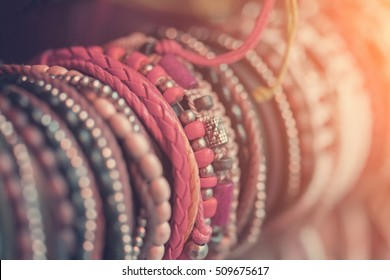Braided leather bracelets with beads in the sunlight, background