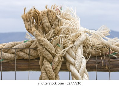 Braided marine ropes tied together against a blue hazy sky