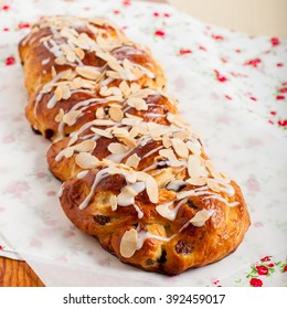 Braided Sweet Bread with Raisins Topped with Sugar Glaze and Flaked Almonds, square