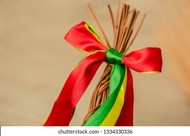 Braided whip made from pussy willow twigs and decorated with red, green and yellow ribbons, a traditional symbol of Czech Easter used for whipping girls and women, blurry background