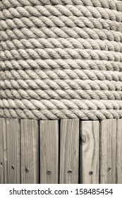 Braided white rope wrapped around a wooden post.