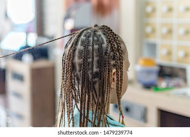 braiding a lot of braids for girl in the beauty salon