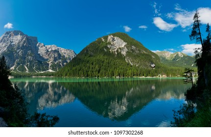 Braies lake in a clear day of summer season with mountains and blue sky in background, Dolomites - Italy