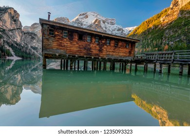 Braies Lake in Dolomites mountains forest trail in background, Sudtirol, Italy. Lake Braies is also known as Lago di Braies. The lake is surrounded by forest which are famous for scenic hiking trails