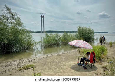 Braila, Romania; June 13, 2021: Young boy playing on a tablet under the umbrella on a sunny day on the Danube shore while others are fishing.