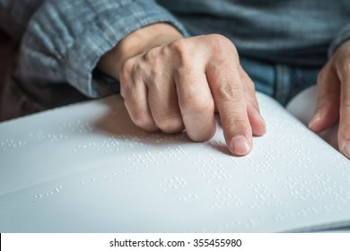 Braille book with visual impaired, low vision, blind person's hand/ finger touching paper texture reading the sign