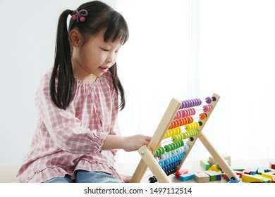 Brain Development At Early Childhood With The Abacus. kindergarten children grabbing colorful wooden abacus. Child's ability concept ,Educational toy