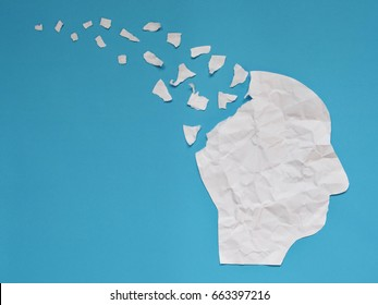 Brain disorder symbol presented by human head made form crumpled paper torn on blue background with copy space. Creative idea for Alzheimer's disease, dementia, memory loss and mental health concept.