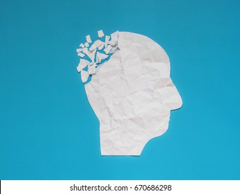 Brain disorder symbol presented by human head made form crumpled paper torn on blue background. Creative idea for Alzheimer's disease, dementia, memory loss and mental health treatment concept.