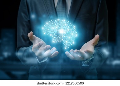 A brain image consisted of different connections with the chip inside is hanging between the businessman's hands at the dark background. The concept is the artificial intelligence and brainstorming.