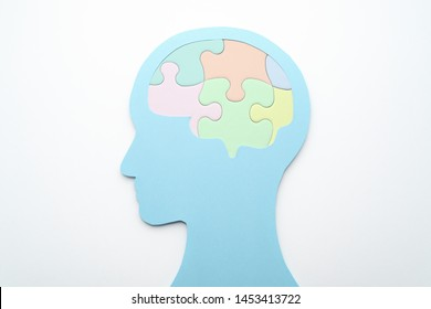 Brain and mental health care concept. Mental management. Head silhouette and brain shaped puzzle pieces on white background.