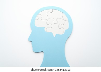 Brain and mental health concept. Mental management. Head silhouette and brain shaped puzzle pieces on white background.