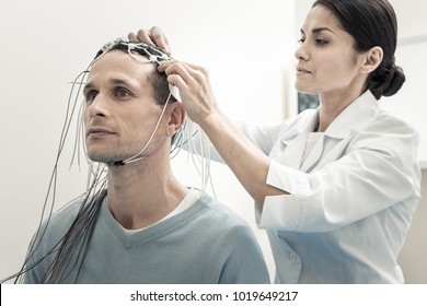 Brain scanning. Professional serious female doctor standing behind her patient and purring electrodes on his head while preparing him for electroencephalogram