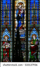 BRAINE-LE-CHATEAU, BELGIUM - JULY 31, 2009: Stained Glass window in the Church of Braine-le-Chateau, Wallonia, Belgium, depicting Saints Peter and John and Mother Mary