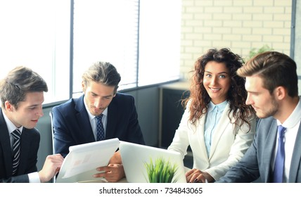 Brainstorm. Group of business people looking at the laptop together. One business woman looking at camera.