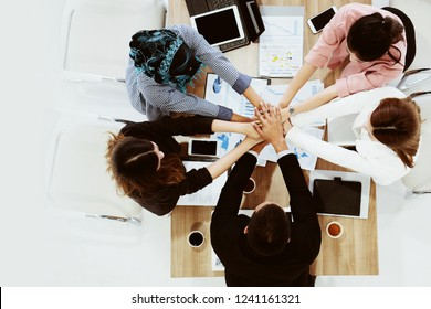Brainstorm Meeting and agreement of Various ethnicity businessman join hand demonstrate harmony for successfully work and achieved goal. Teamwork require clear division work to achieve the goal.