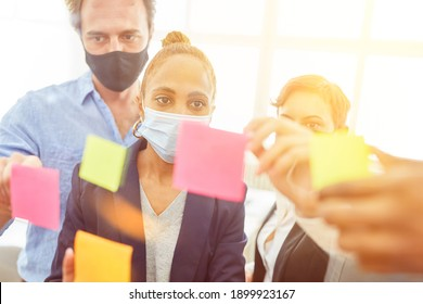 Brainstorming business meeting in the office with face masks because of coronavirus and Covid-19
