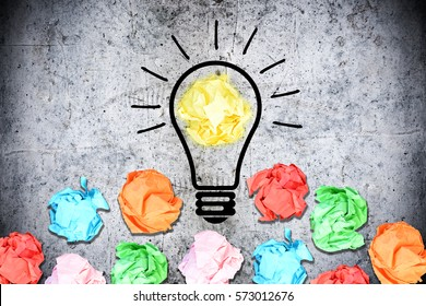 Brainstorming concept with multiple crumpled pieces of colorful paper surrounding a light bulb on concrete background