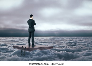 Brainstorming concept with thinking businessman standing on brick pedestal in dull cloudy sky
