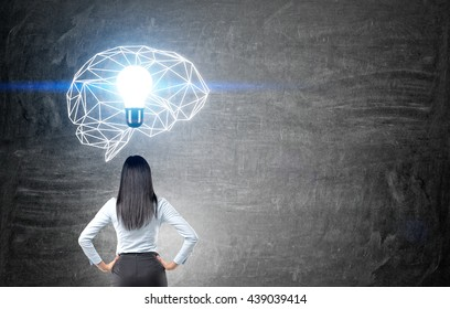 Brainstorming concept with thoughtful businesswoman looking at chalkboard with illuminated polygonal brain sketch and abstract light bulb